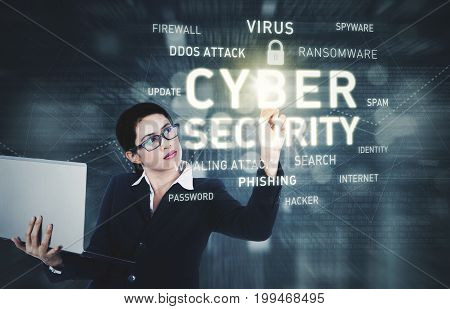 Image of pretty businesswoman holding a laptop computer while touching a text of cyber security on the virtual screen