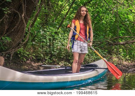 A young girl on a kayak with a paddle in a forest on a stream with lianas