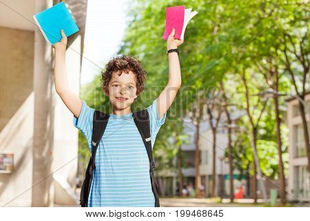 Portrait of schoolboy lifting textbooks and smiling in front of a school