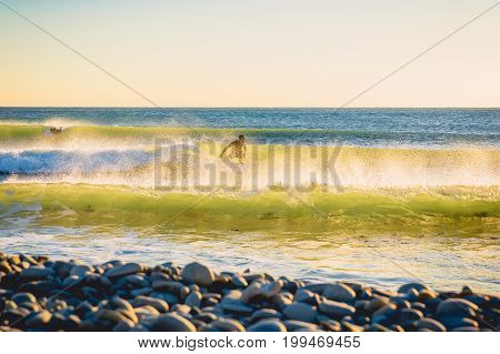 Surfer ride on wave at sunset or sunrise. Surfer in ocean and waves