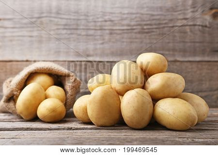 Ripe potatoes on the grey wooden table