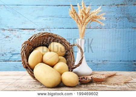 Potatoes In Wicker Basket With Pepper On Wooden Background