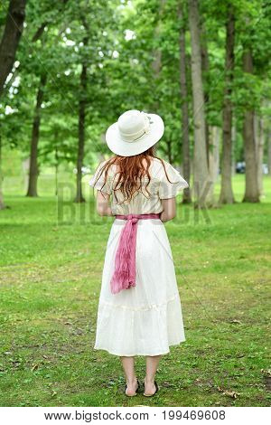 back of vintage redhead woman with hat in park