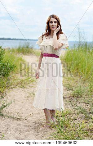 portrait of redhead woman on sand beach path