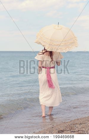 back of vintage woman on beach with parasol