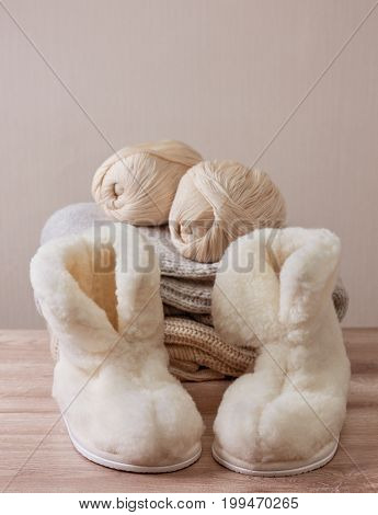 Pair of warm winter sheepskin slippers (alpaca) wool yarn on a pile of warm woolen clothes (Selective focus)