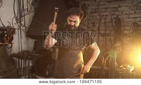 Portrait of a blacksmith in the working atmosphere. A man works with molten metal in the forge