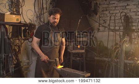 Man works with molten metal in the forge poster