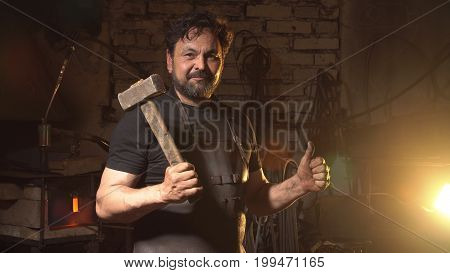Cool blacksmith portrait with beard in workshop.