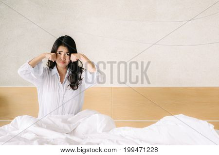 Unhappy Asian woman is crying in bedroom in morning.