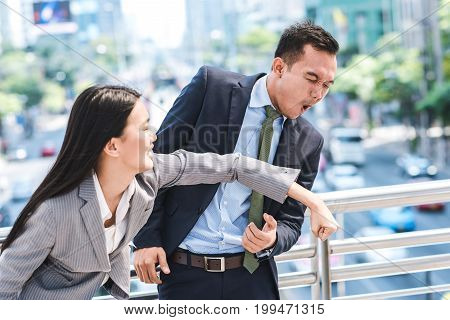 Angry Asian businesswoman punching colleague businessman in face outdoor