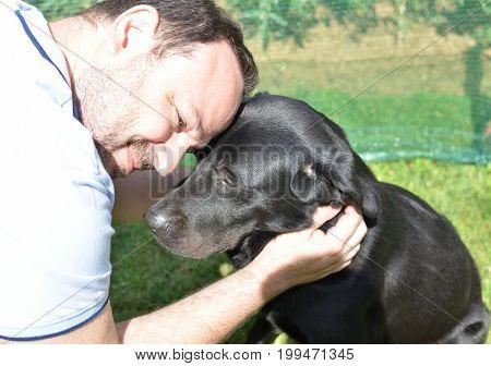 Man Cuddling His Black Dog