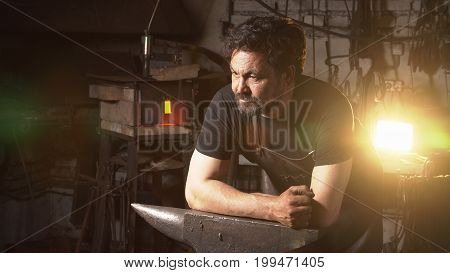 Portrait of a blacksmith in the working atmosphere. A man works with molten metal in the forge poster