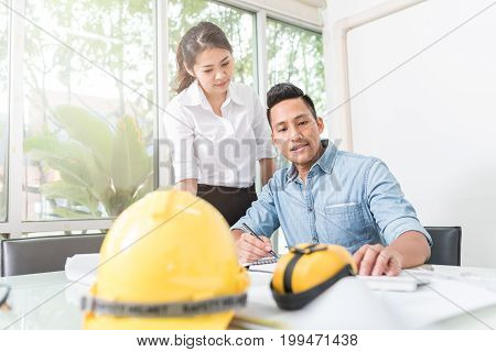 Engineer and architect discussing about new construction project at table with equipment in office