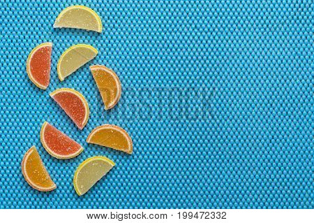 Multicolored marmalade on a blue background. Marmalade is citrus slices