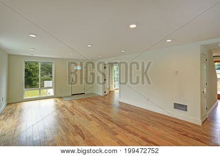 Empty Entrance Hall With Polished Hardwood Floor And White Walls