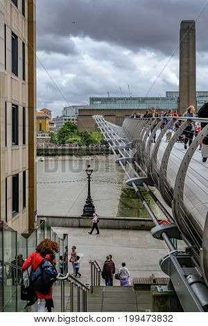 London United Kingdom - August 3 2017: Tourists crossing over the Millennium Bridge. Side view of the bridge looking towards The Tate Modern.