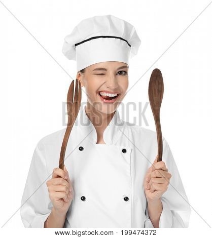 Young female chef with utensils on white background
