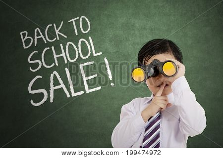Little cute boy using a binocular while showing forefinger over lips with text of back to school