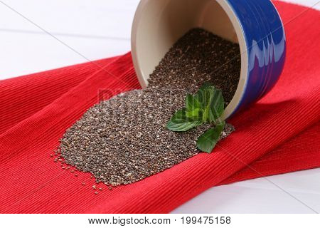 bowl of chia seeds spilt out on red place mat - close up