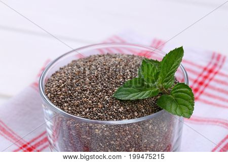 glass of chia seeds on checkered dishtowel - close up