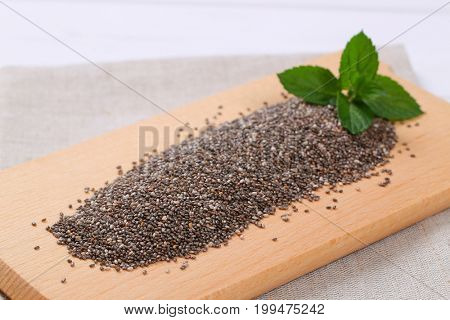 pile of chia seeds on wooden cutting board - close up