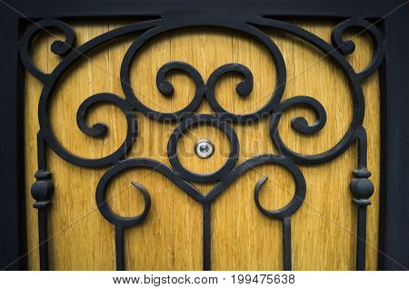 Wooden door with a pattern of iron and peephole room