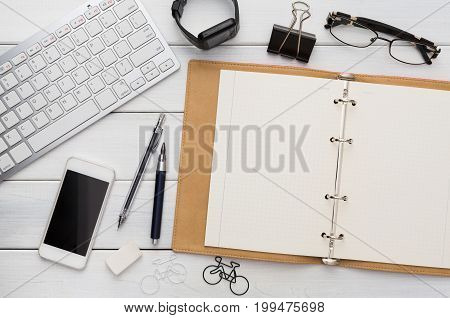 Modern office background. Stationery, open notepad, smart watch, keyboard, glasses and mobile on white wooden table. Top view on stylish workspace with copy space on blank textbook