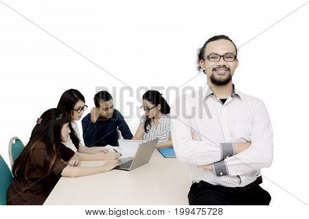 Portrait of a young male business leader folded hands while his team discussing on the background