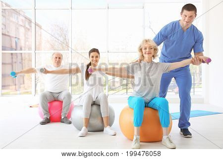 Physiotherapist working with elderly patients in modern clinic