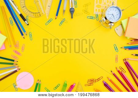 back to school or office styed scene with multicolored school supplies on yellow background