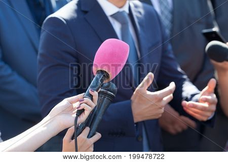 Media interview. Hand gesture. Business person or politician.
