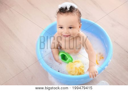 Little baby washing in bath basin at home