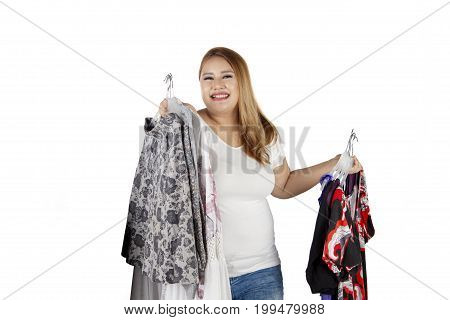 Portrait of happy obese woman holding many clothes and smiling at the camera isolated on white background