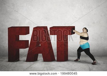 Obese woman punching word of fat while wearing sportswear