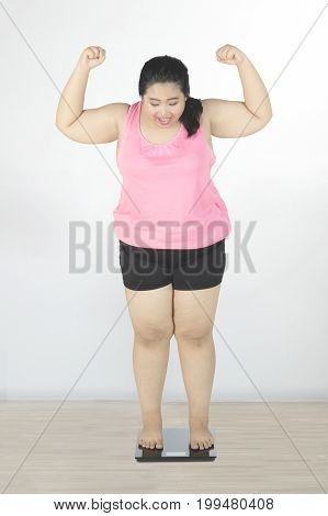 Obese woman success to lose weight while standing on weight scale and lifting hands