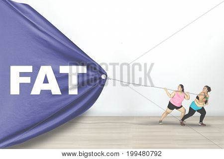 Two obese young women dragging a big flag with Fat text while wearing sportswear