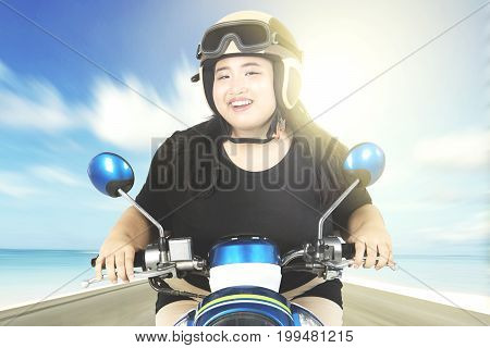 Overweight woman using a helmet while smiling at the camera and driving a motorcycle on the beach