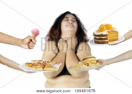 Image of overweight woman rejecting unhealthy food offered by someone isolated on white background