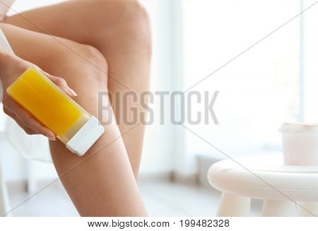 Beautiful young woman removing hair with wax at home