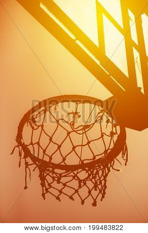 Basketball hoop on amateur outdoor basketball court for streetball against strong summer sunlight