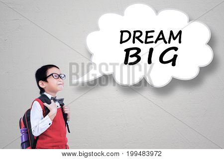 Male elementary school student wearing uniform and carrying bag with Dream Big text on speech bubble