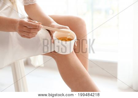 Beautiful young woman removing hair from legs at home