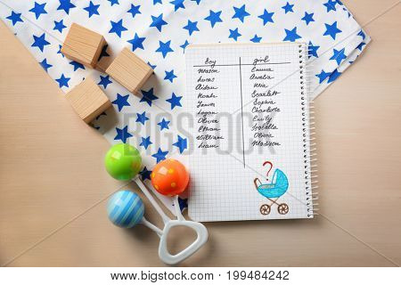 Composition with list of baby names in notebook on wooden background