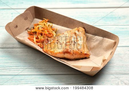 Cardboard box with delicious fish and vegetables on table