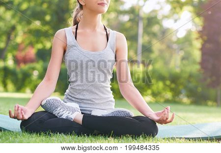 Cropped shot of a young woman smiling while meditating outdoors at the park sitting in lotus position yoga practicing exercising meditation peaceful harmony concept.