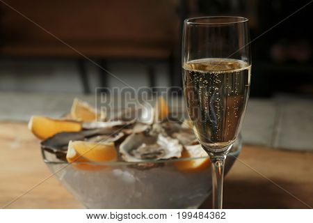 Glass with champagne and blurred oysters in bowl on background