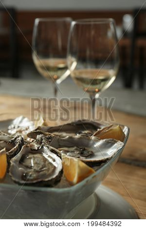 Delicious oysters with slices of lemon on ice cubes in bowl