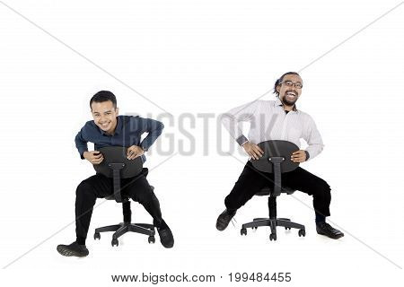 Two businessmen sitting on the chair while having fun together isolated on white background