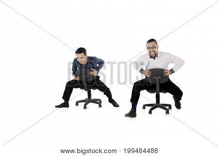 Two businessmen sitting on the chair while racing in the studio isolated on white background